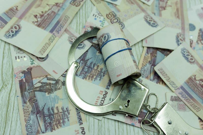 证据从一位腐败警察被占领了 警察在皮革盖子和金钱证章在桌上 反腐 免版税库存照片
