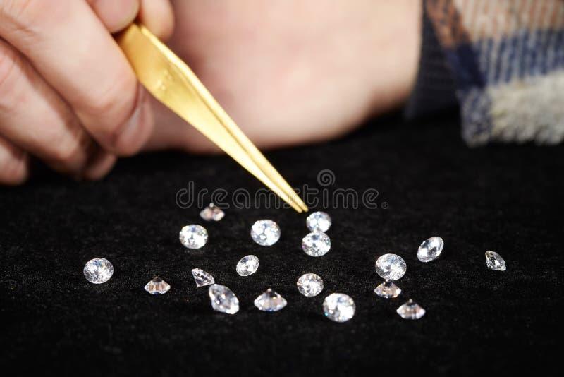 评估成交的金刚石的走私贩宝石在天鹅绒垫 免版税库存图片