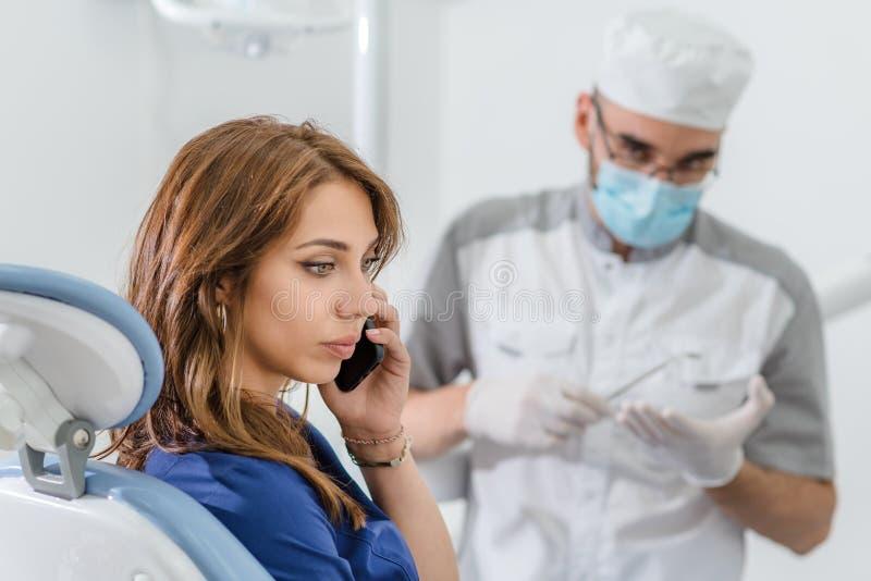 诊所的女孩在正牙医生的招待会谈话在电话和忽略医生 免版税图库摄影