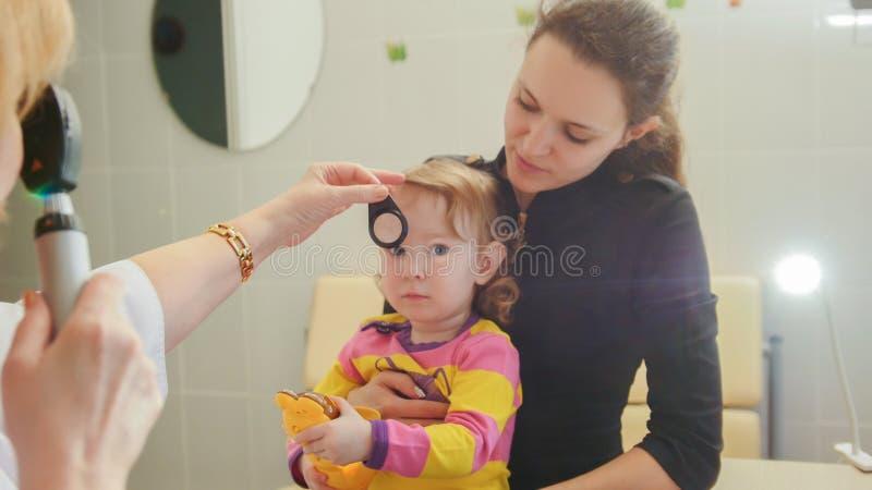 诊所的妇女验光师检查眼力在小女孩-儿童` s眼科学 免版税库存图片