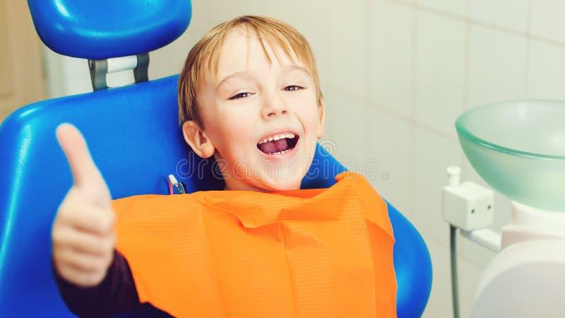 诊所看牙的牙医 坐在牙椅上的快乐男孩 儿童在治疗牙齿时 库存照片