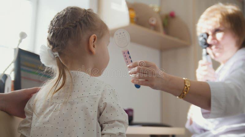 诊断在儿童` s眼科学-验光师诊断小女孩方面 免版税库存照片