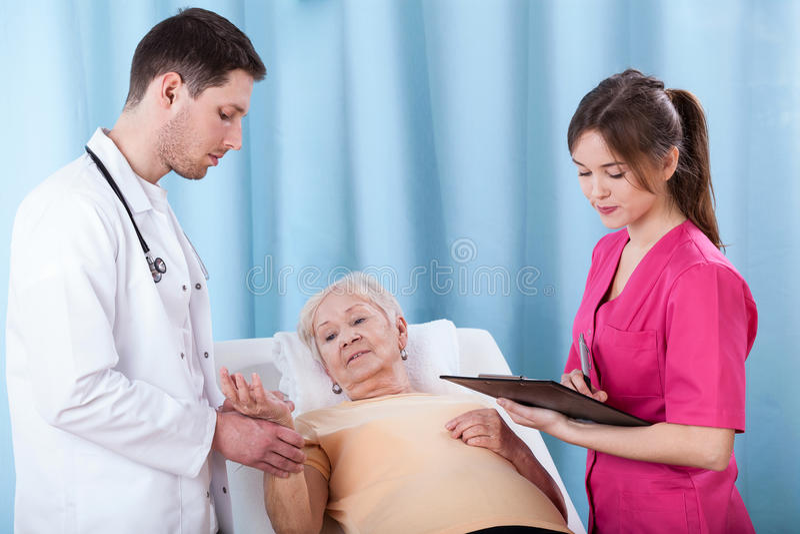 诊断年长妇女的医生 免版税库存图片