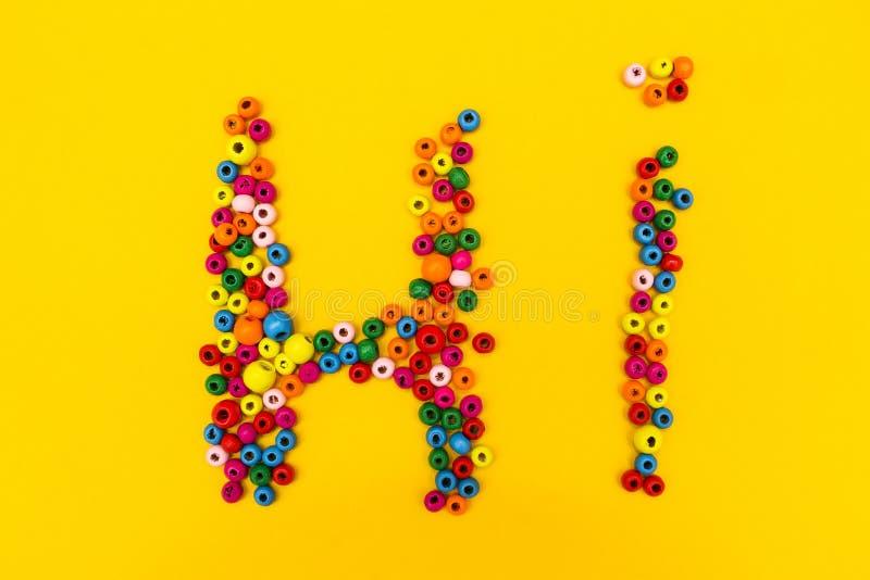 词'喂'从在黄色背景的多彩多姿的圆的玩具 图库摄影