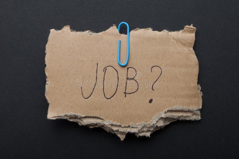 词'工作?'在纸板箱片断在黑背景的 免版税图库摄影