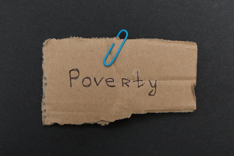 词'贫穷'在老纸板 库存照片