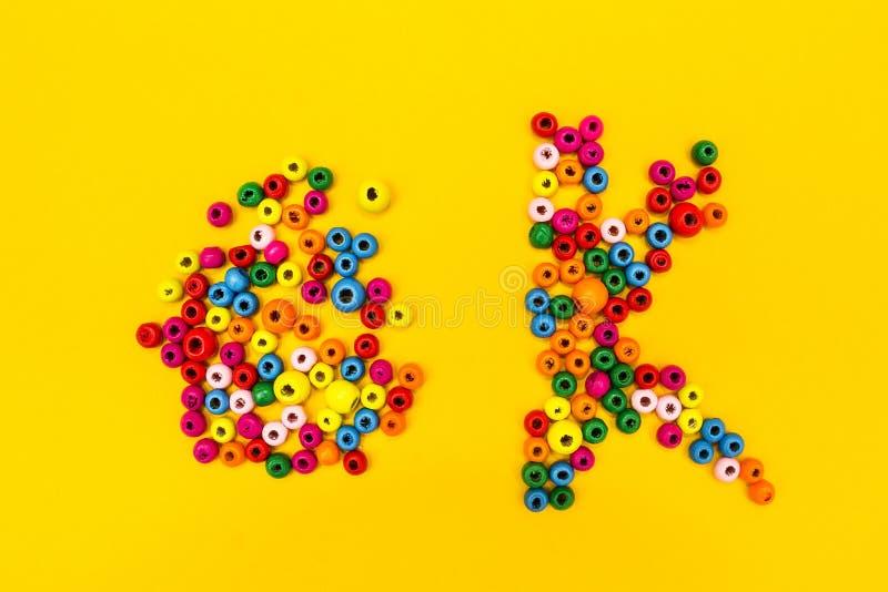 词'ok'是从在黄色背景的多彩多姿的圆的玩具 库存照片