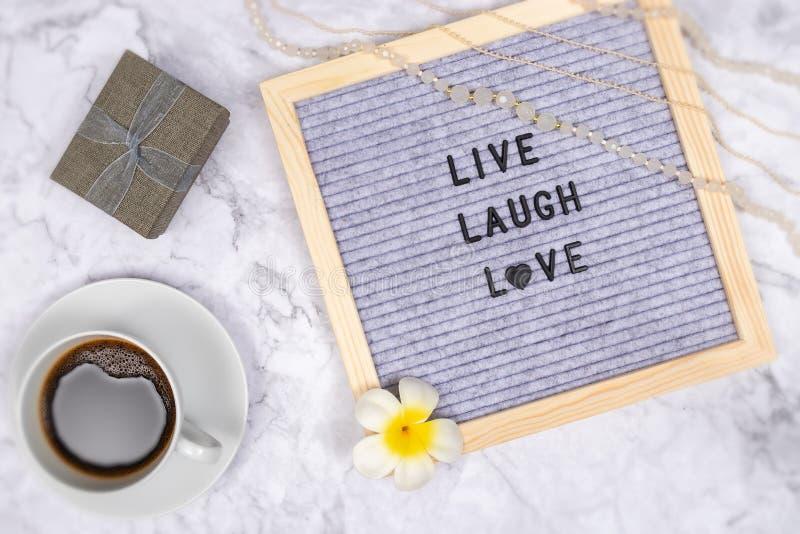 词与咖啡杯和礼物盒,与花的装饰居住在信件板的笑爱在白色大理石书桌背景 免版税库存照片