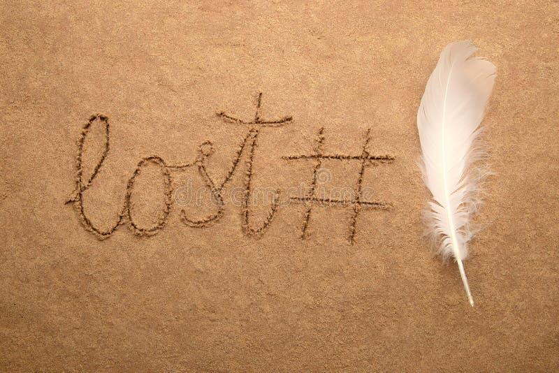 词丢失了,回锅碎肉标记和羽毛在沙子背景 图库摄影