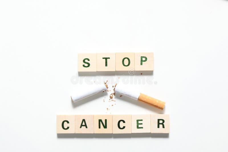 词停止癌症被隔绝的被做木块和一根残破的香烟在白色背景 图库摄影