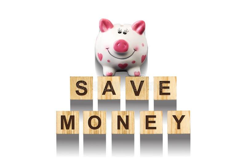 词在与存钱罐的木建筑立方体存金钱,组成由信件 白色背景,被隔绝的概念事务, fi 库存图片