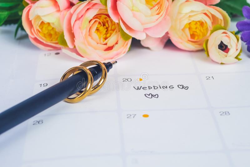 词婚礼对与结婚戒指的提示婚礼那天在日历计划 免版税图库摄影