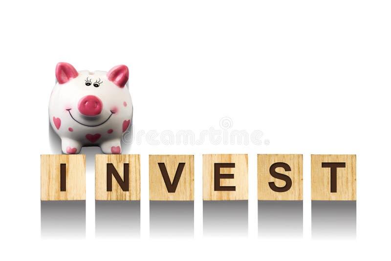 词投资,组成由在木建筑立方体的信件与存钱罐 白色背景,被隔绝的概念事务, financ 库存图片