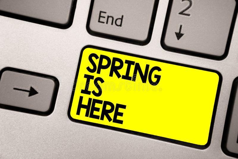 词文字文本春天在这里 在冬天季节以后的企业概念到达了享受自然花太阳键盘黄色ke 免版税库存照片
