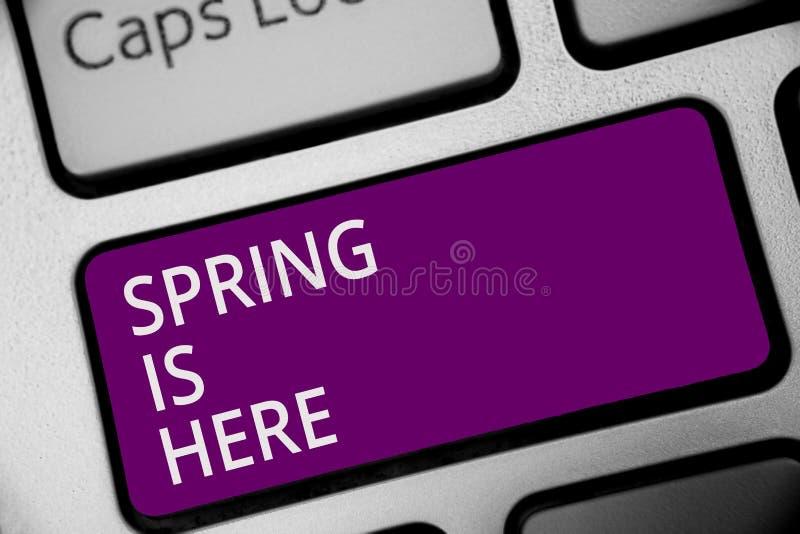 词文字文本春天在这里 在冬天季节以后的企业概念到达了享用自然花太阳键盘紫色ke 库存图片