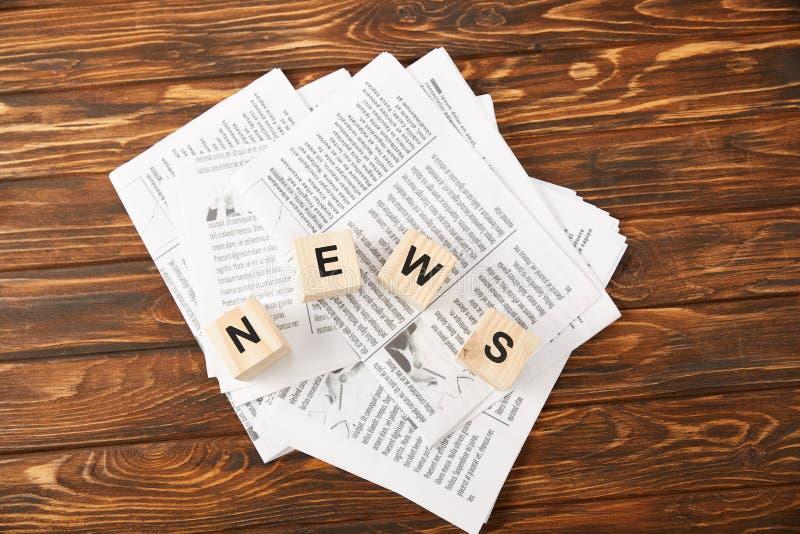 词新闻顶视图由字母表立方体制成在报纸堆在木背景 免版税库存照片