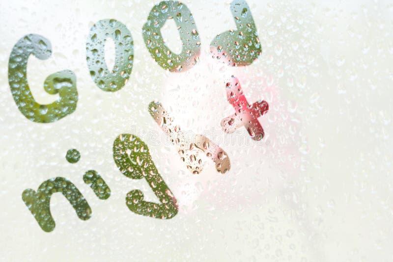 词晚安的条纹的形状的手指图画一块透亮,misted玻璃的 春雨雨珠  库存图片
