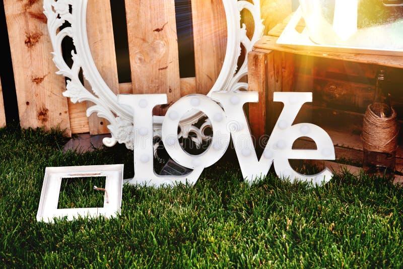 词爱组成由在日落的白色信件 装饰提案 婚礼,在外部的庆祝计划  库存图片