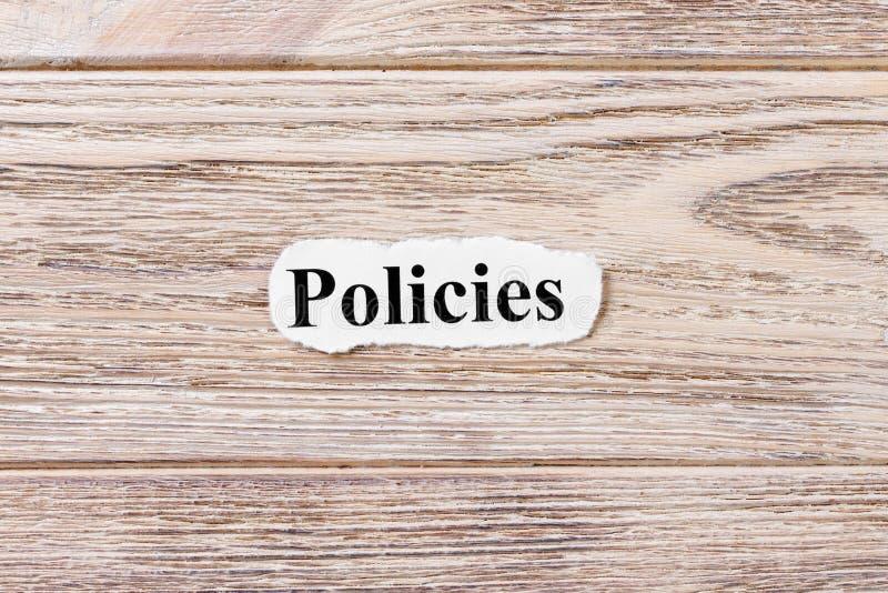 词的政策在纸的 概念 政策的词由于木背景的 库存照片