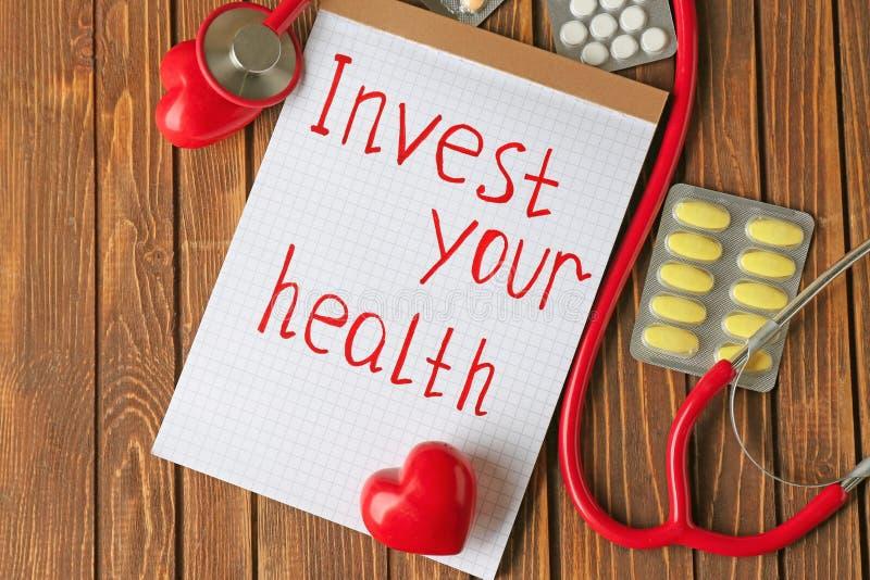 词组投资在纸片写的您的健康、听诊器和药片在木背景 免版税库存照片