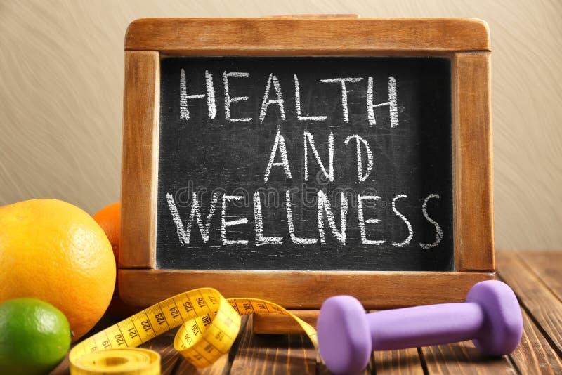 """词组\""""健康和健康\""""写在黑板、果子和哑铃在木桌上 免版税库存图片"""