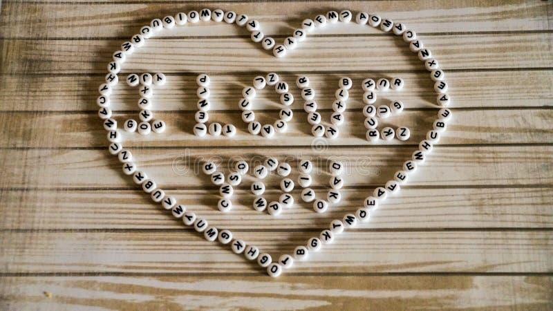 词组`我爱你`大心脏组成由白色,圆,木表面上的塑料块 免版税图库摄影