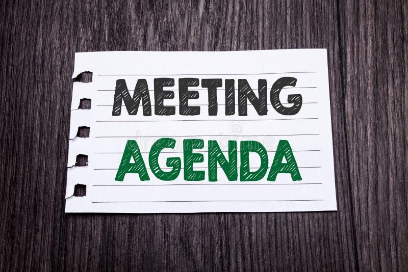 词,写会议议程 企业在黑暗的木backgrou的稠粘的便条纸写的日程表计划的企业概念 库存照片
