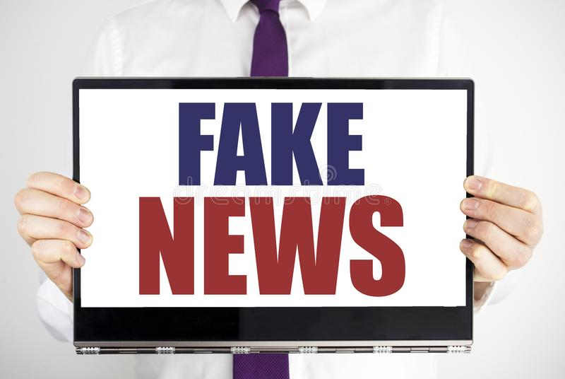 词,写假新闻 在片剂膝上型计算机写的骗局新闻事业的企业概念举行由人弄脏了背景 Busi 库存照片