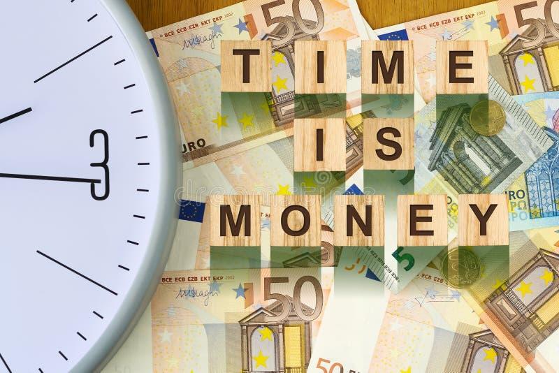 词,时间是金钱组成由在木积木的信件以欧洲钞票为背景 概念事务, fina 免版税库存图片