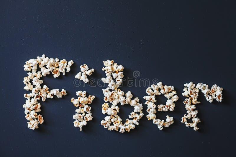词`纤维`由新鲜的玉米花制成在黑暗的铜铍绘了表面 免版税图库摄影