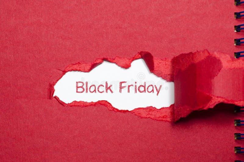 词黑色出现在被撕毁的纸后的星期五 库存图片
