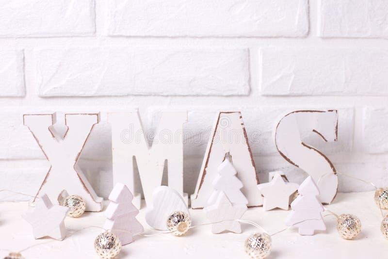 词Xmas由木信件、木星、心脏和树,彩色小灯做了近由白色砖墙 库存照片
