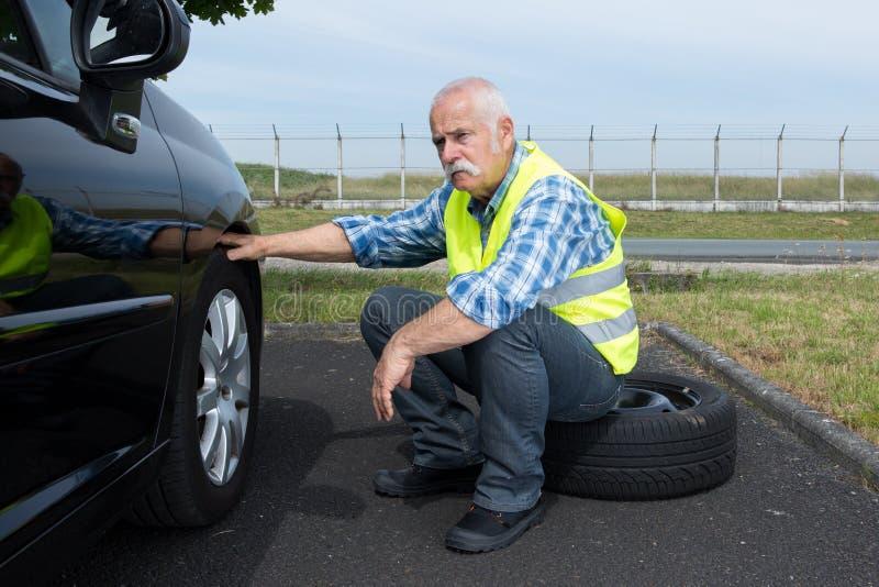 试图被劝阻的老人改变轮胎 库存图片