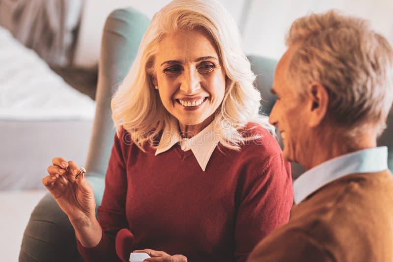 试穿新的圆环的微笑的年迈的妇女 库存照片