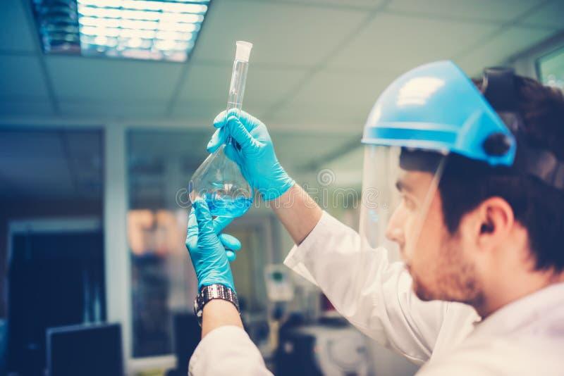 试管在科学家手上 分析蓝色液体的构成和结构年轻医生细节 免版税库存图片