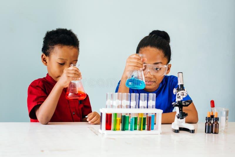 试验在学校化学实验室的好奇黑人孩子 免版税库存照片