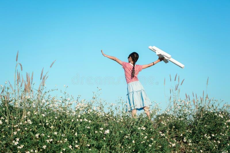 试验女孩孩子想象到未来使用的玩具空中飞机在outd 库存照片