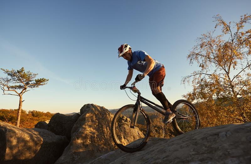 试验自行车的男性骑自行车者在户外冰砾上面  免版税库存照片