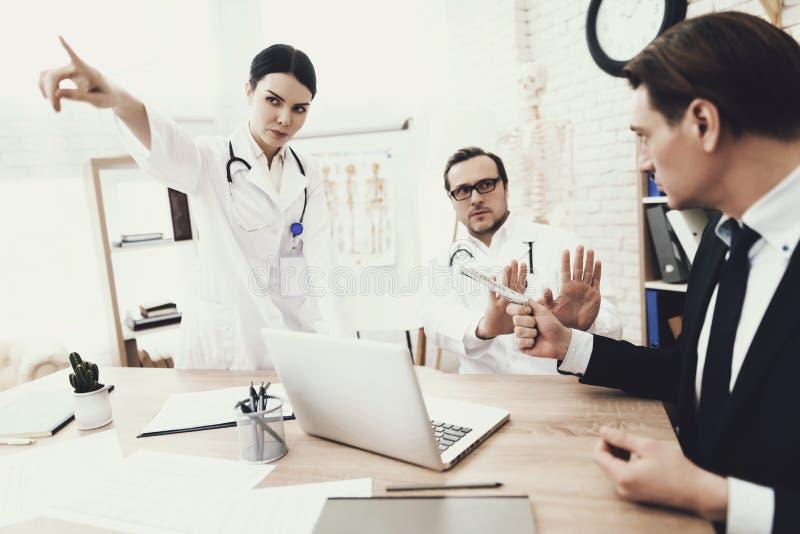 诚实的医生和护士在医疗办公室拒绝收取从患者的贿款 免版税库存照片