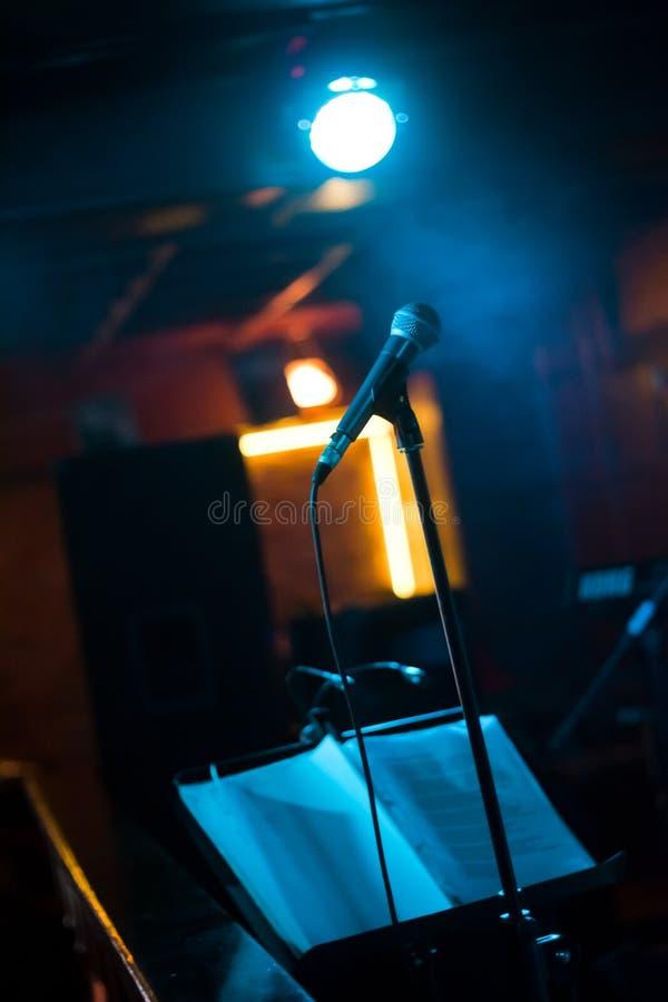 话筒和立场在阶段准备好在开始一个音乐会前在客栈,低灯,低调照片 免版税库存照片