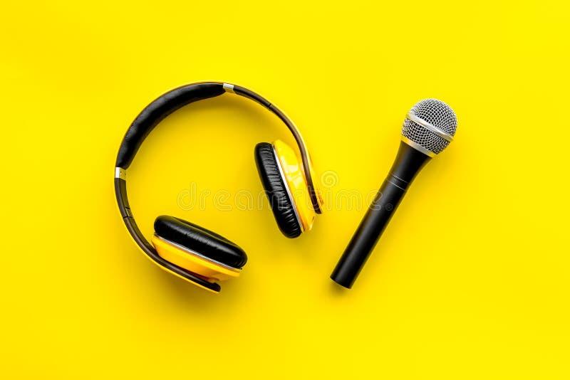 话筒,博客作者、新闻工作者或者音乐家工作的耳机在黄色背景顶视图 免版税库存图片