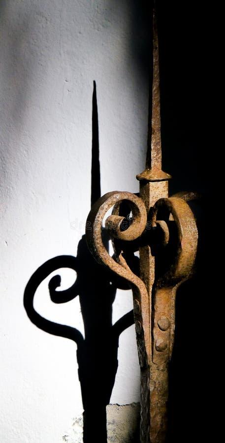 详述和有它的阴影的老装饰和生锈的铁篱芭 免版税库存图片