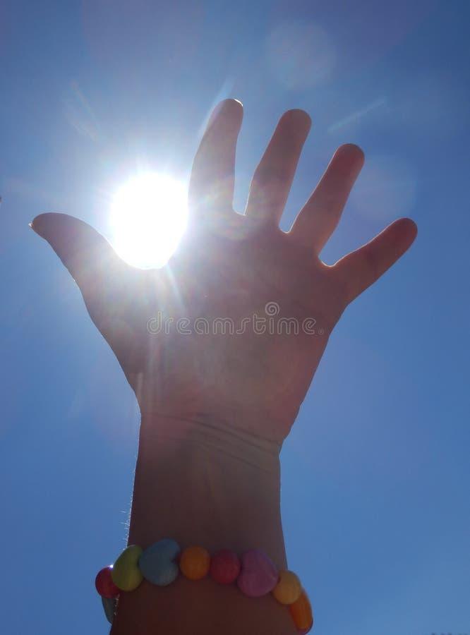 详述妇女手传染性的太阳光芒和蓝天彩色照相  免版税库存图片