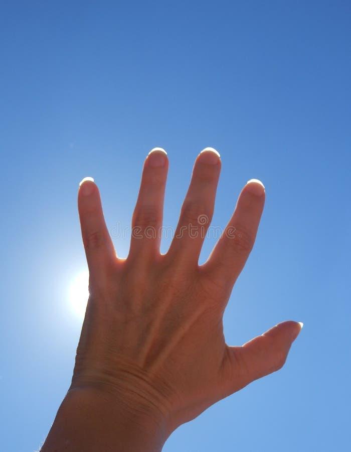 详述妇女手传染性的太阳光芒和蓝天彩色照相  图库摄影