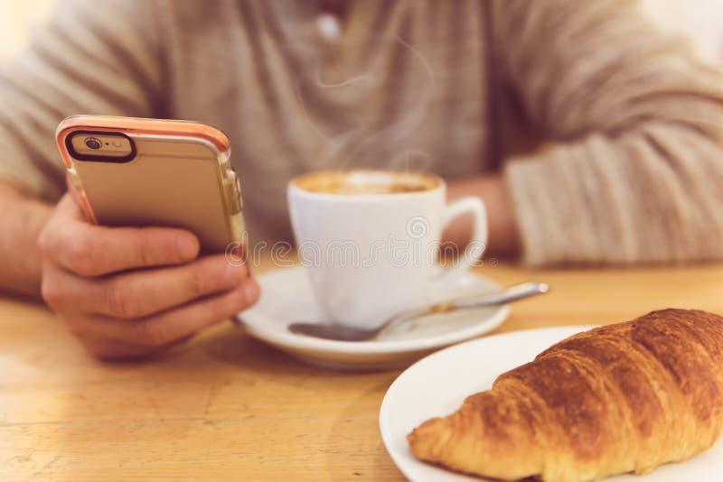 详述无法认出的人饮用的咖啡和拿着巧妙的电话的图象,当食用早餐在餐馆时 免版税库存照片