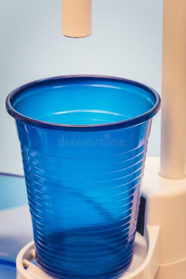 详述紧密与一个蓝色杯子的一个牙医水槽 图库摄影