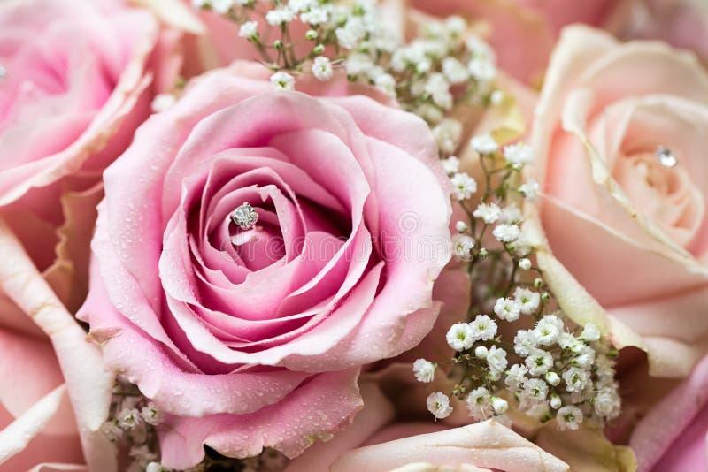 详细的花束的一张色的宏观照片与桃红色玫瑰、白色小花和假金刚石的在玫瑰的中心 图库摄影