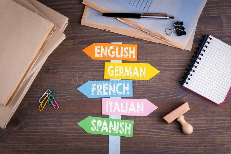 语言概念 在一张木书桌上的纸路标 库存照片