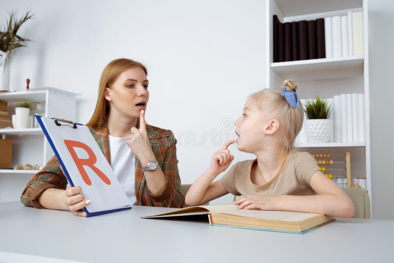 语言矫正概念 与女性治疗师训练发音的耐心孩子 库存图片
