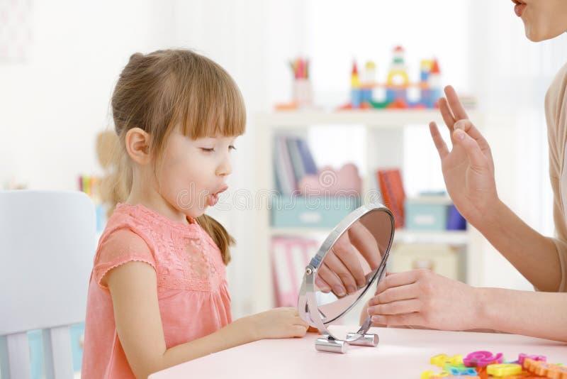 语言矫治者的逗人喜爱的小女孩 免版税库存图片